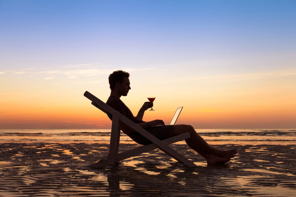 Man working from the beach with a laptop