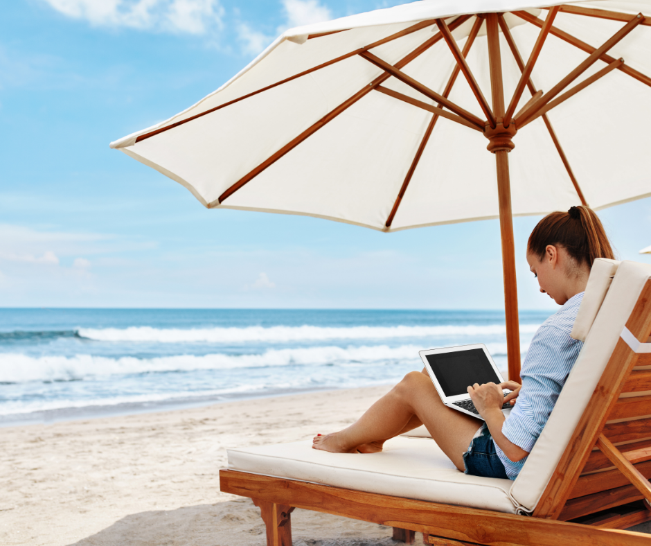 Women working on beach with laptop